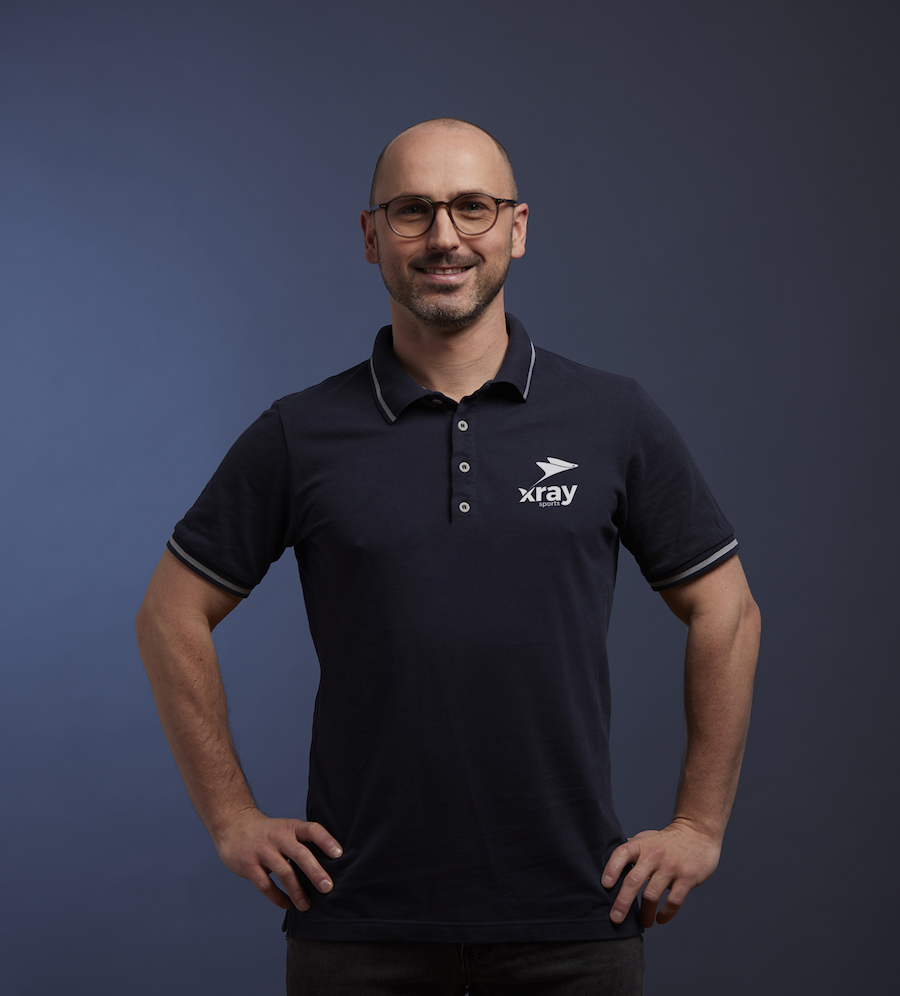 Alexander Steinhart trägt ein blaues Polohemd mit dem xray sports Logo als Aufdruck auf der linken Brust.